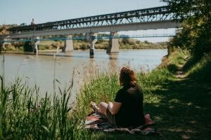 Person sitting on the grass with a bridge in the background