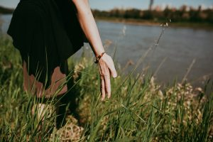 Woman standing in the grass near a body of water